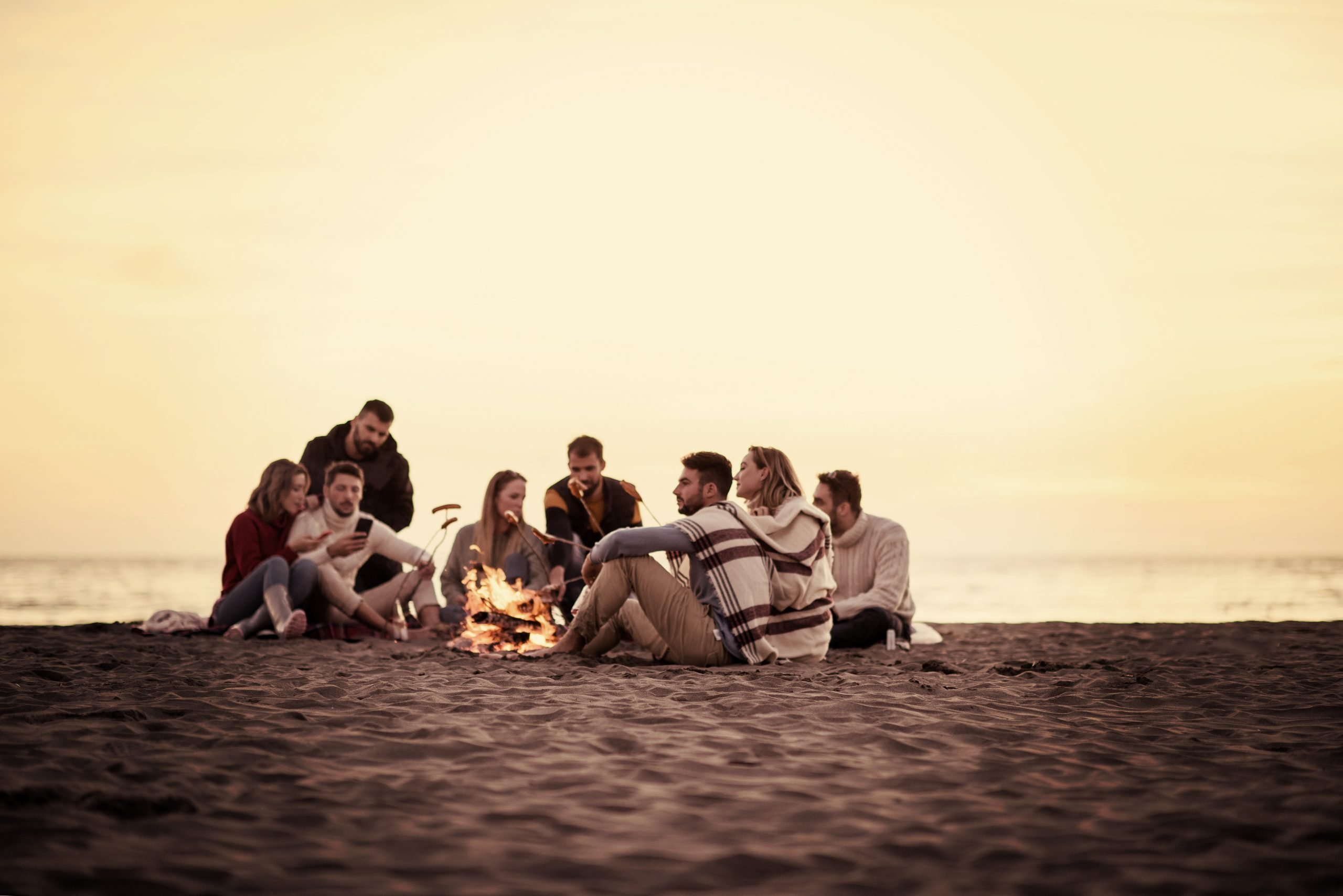 Group,Of,Young,Friends,Sitting,By,The,Fire,At, Camping
